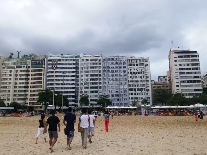 Tourists walking on the white sandy beaches of Rio de Janeiro, Brazil royalty free stock photos