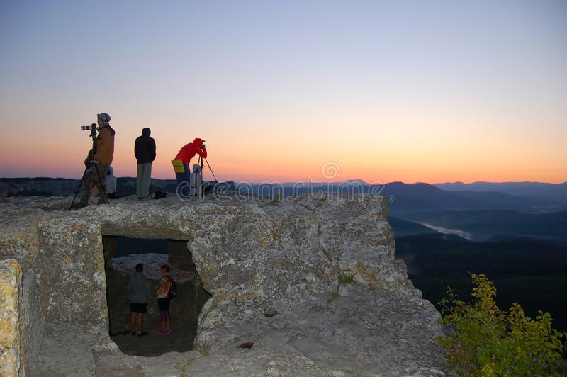 Tourists watch the sun rise on the mountain. In hiking royalty free stock photo