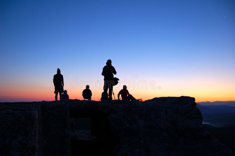 Tourists watch the sun rise on the mountain. Tourists in hiking watch the sun rise on the mountain stock photos