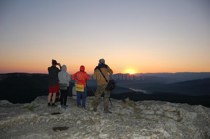 Tourists watch the sun rise on the mountain. In hiking stock photography