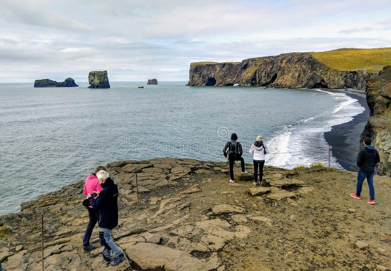 Tourists watching Dyrholaey Arch in south Iceland. Tourists watching Dyrholaey Arch on Atlantic Ocean in south Iceland royalty free stock photography