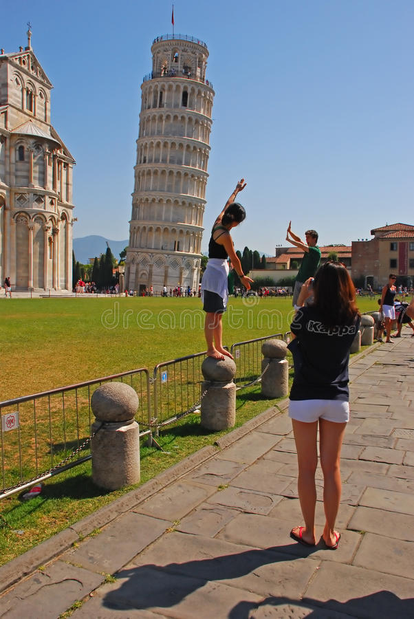 Tourists were mimicking the action of pushing Leaning Tower of Pisa Staight royalty free stock photography