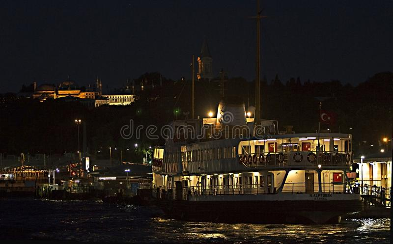A public ferry called `Vapur` at Eminonu Port under the Topkapi Palace of the Ottoman Empire by night. Tourists who seek for a contemporary version of 1001 royalty free stock photos