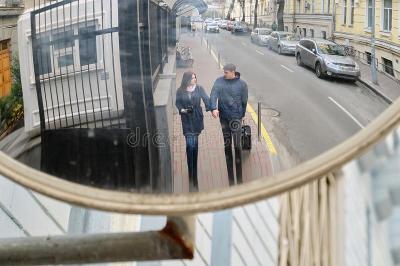 Tourists young couple walking around the city with camera suitcase. Focus in specific street mirror, youth traveling royalty free stock photos