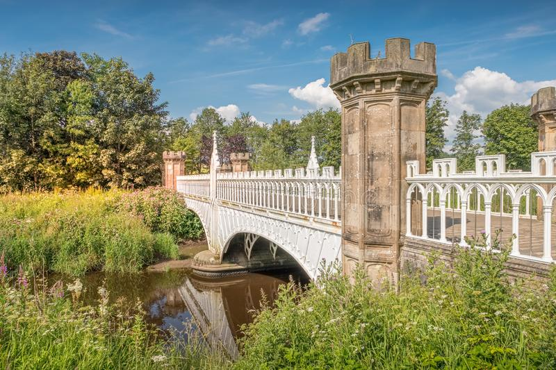 The Tournament Gothic Bridge with Baronial Piers and Iron Archetecture. Eglinton, Irvine Scotland. Irvine, Scotland, UK - July 15, 2019: Eglinton Park Autumn and royalty free stock image