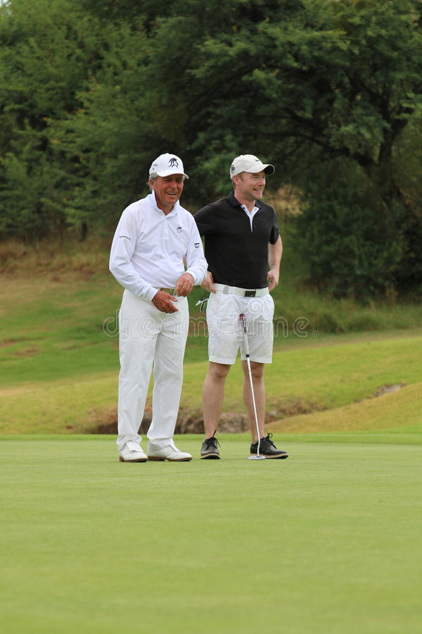 Tournament presenter and grand master Gary Player cracking a joke with team mate, singer, songwriter Ronan Keating on November stock photography