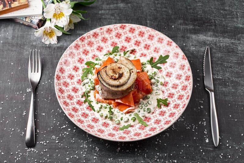 Tournedo van forel met wortelnoedels met groene erwten, op een witte plaat horizontale, selectieve nadruk Dieet menu Vissenmenu stock fotografie