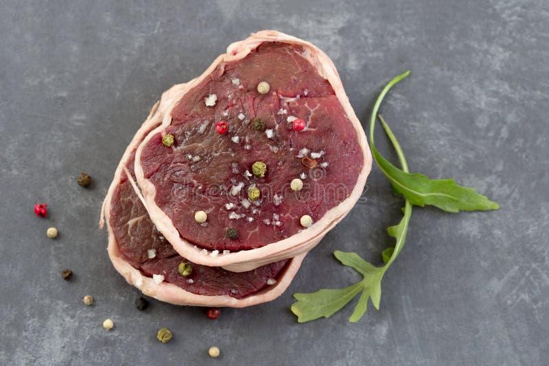 Tournedos: een kleine ronde dikke besnoeiing van een filet van achtergrond van de rundvlees de grijze lei boven mening stock fotografie