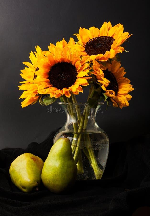 Tournesol, vase et poire photos stock
