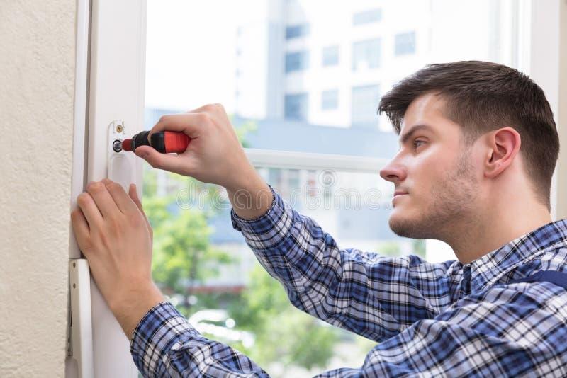 Tournevis de Fixing Window With de bricoleur photo stock