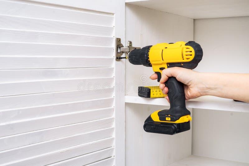Tournevis jaune dans une main femelle Installation des charnières de meubles sur la porte d'armoire image stock