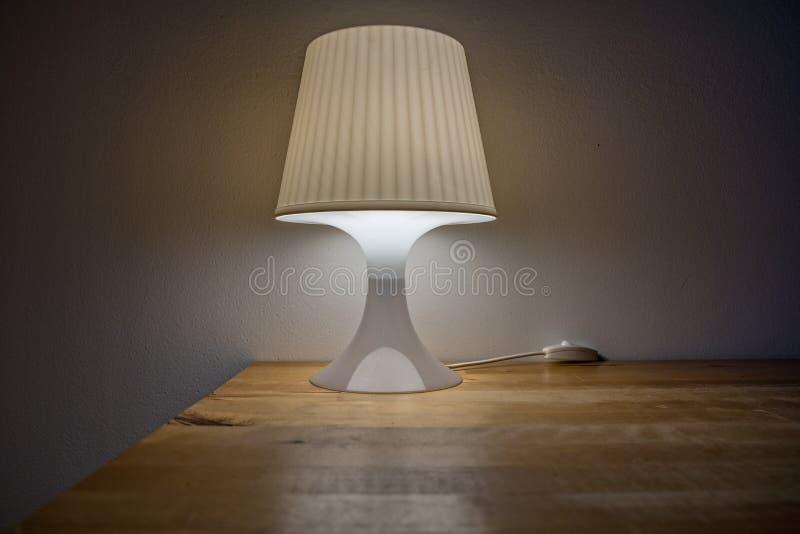 Tournez dessus la lampe de chevet est sur la table photo libre de droits