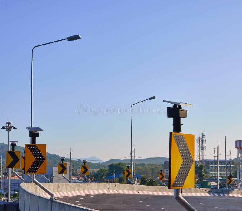 Tournez la route droite de signe avec le ciel bleu clair image libre de droits
