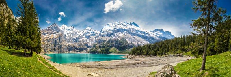 Tourquise surpreendente Oeschinnensee com cachoeiras, o chalé de madeira e os cumes suíços, Berner Oberland, Suíça