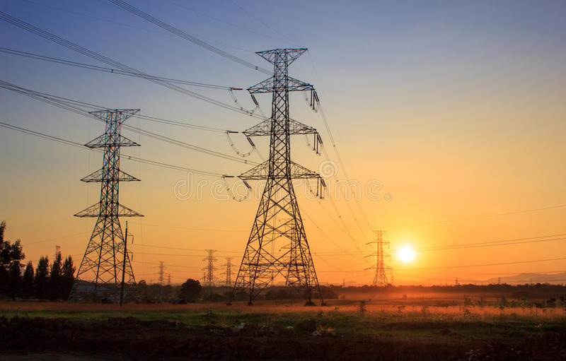 Tours électriques à haute tension pendant le coucher du soleil images libres de droits