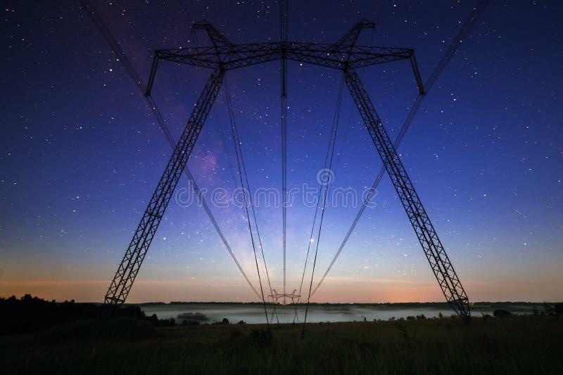 Tours énormes de ligne électrique sur le champ la nuit étoilé été photo stock