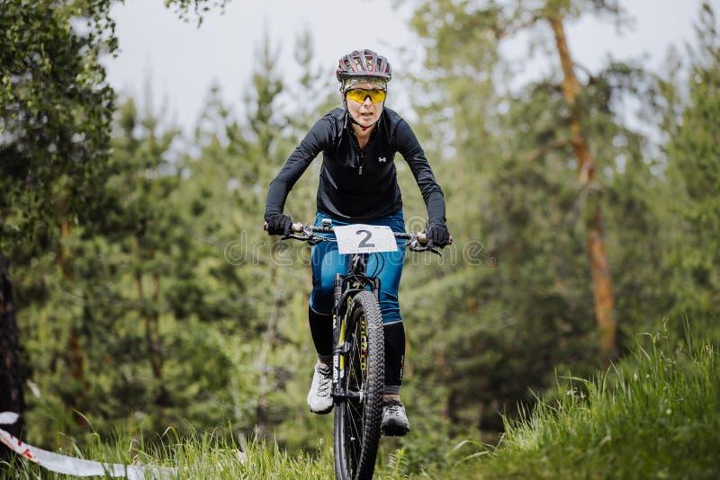Tours de cycliste d'athlète de jeune fille par la forêt images stock