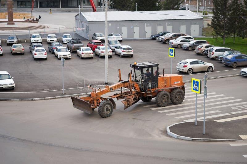 Tours de niveleuse sur la route urbaine après le parking photo libre de droits