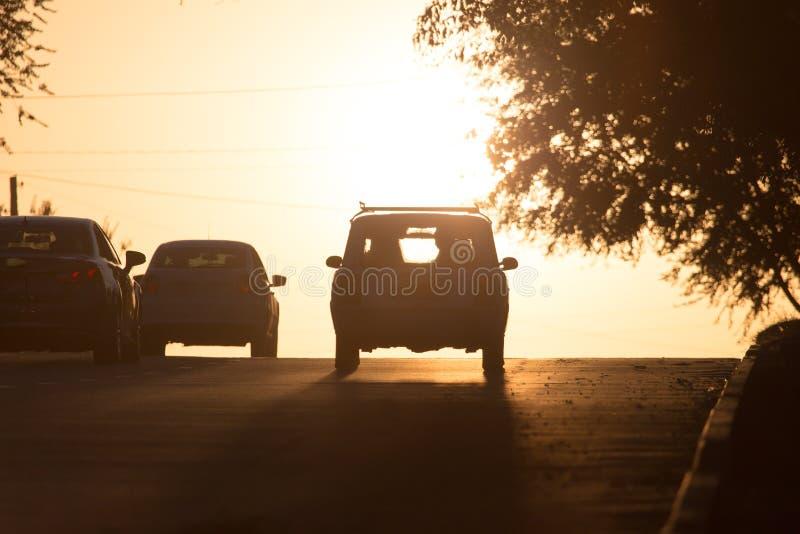 Tours de voiture sur la route au coucher du soleil photographie stock