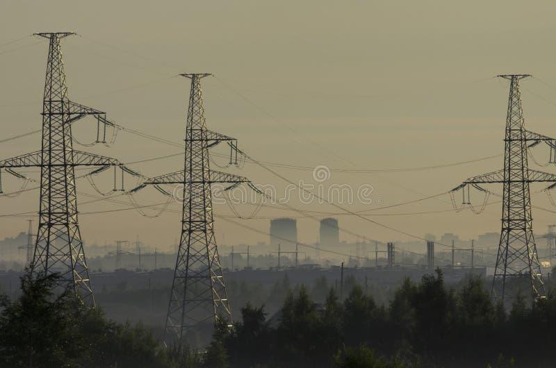 Tours des lignes électriques dans le brouillard avant l'aube images stock