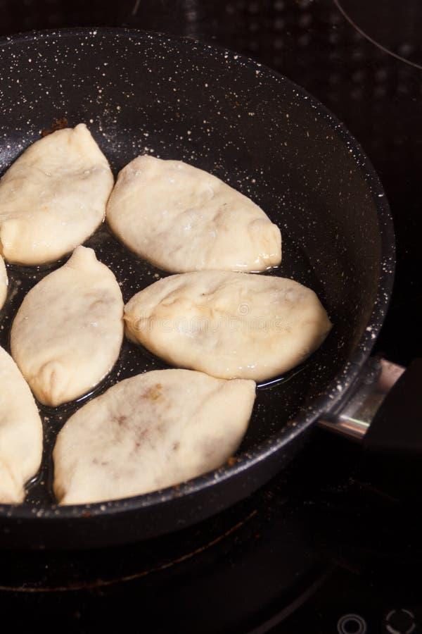 Tourtes à la viande, sautées en huile de ébullition petits tartes crus dans une poêle avec de l'huile chaude photos stock