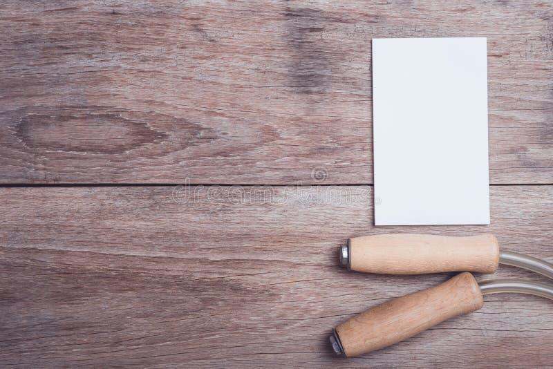 Touwtjespringen en leeg document op de houten mening van de lijstbovenkant stock afbeeldingen