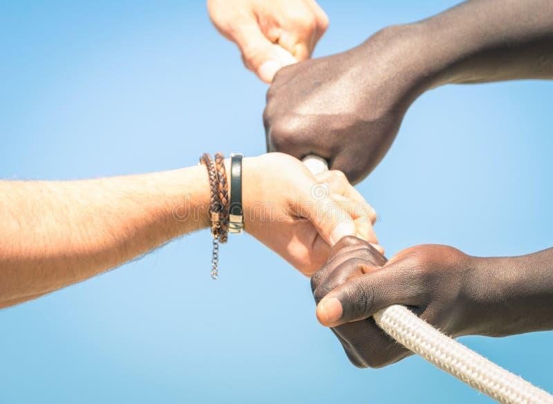 Touwtrekwedstrijd - Concept multi etnische unie tussen verschillende rassen samen stock foto's