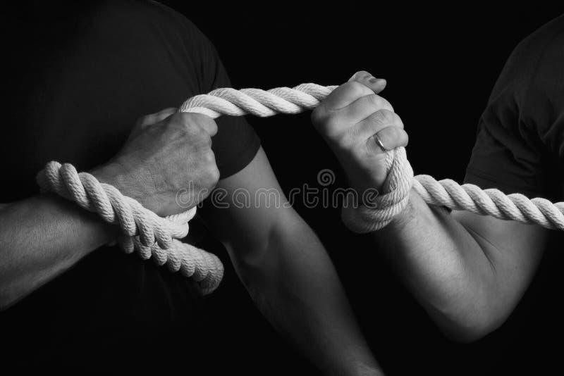 Touwtrekwedstrijd De mensen halen een kabel op een zwarte achtergrond aan stock fotografie