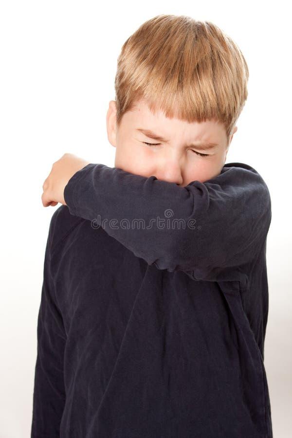 Toux d'enfant/éternuant dans le coude photographie stock