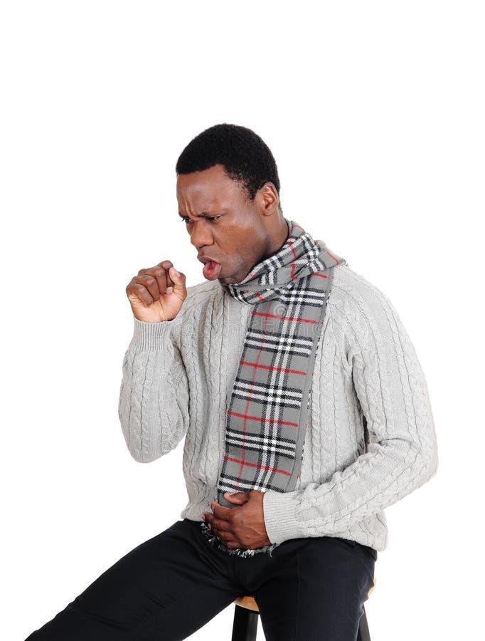 Toux du jeune homme s'asseyant avec l'écharpe photographie stock