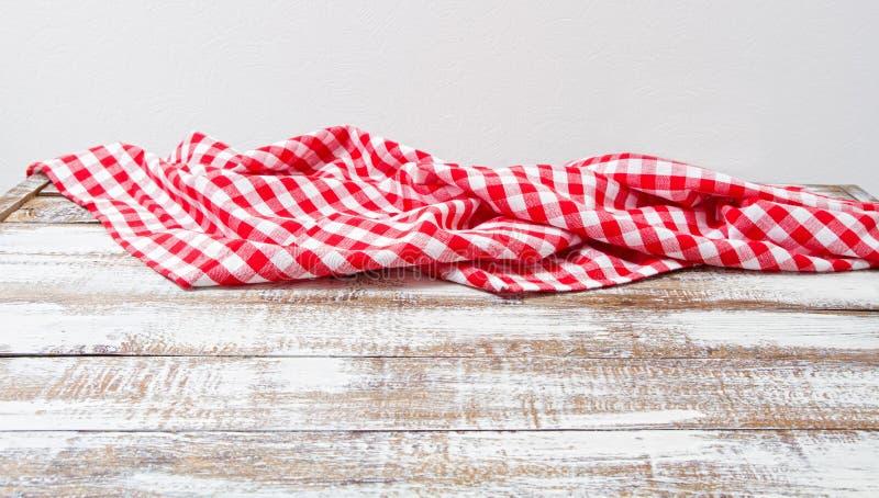 Tovaglia a quadretti sgualcita su una tavola di legno, falsa su immagini stock