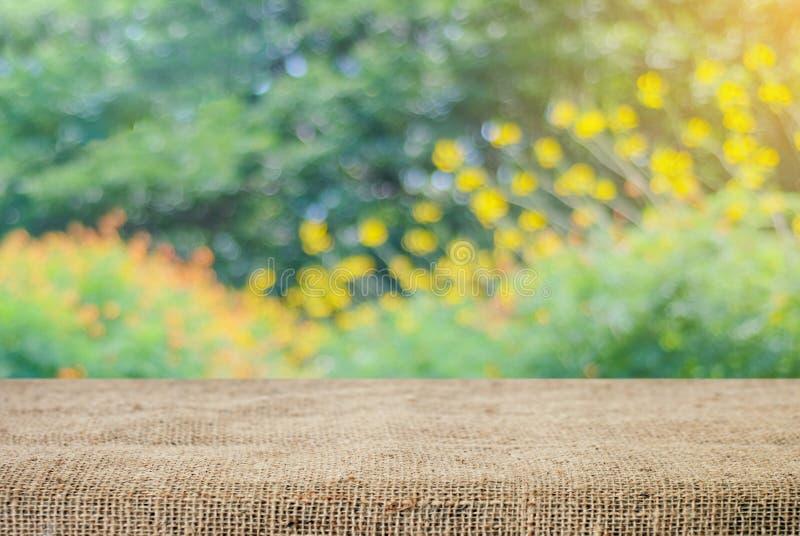 Tovaglia vuota del sacco e della tavola sopra l'albero della sfuocatura con il backgr del bokeh fotografia stock libera da diritti