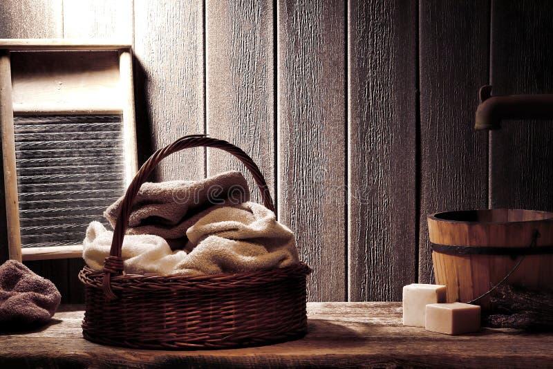Tovaglioli asciutti in vecchio cestino di vimini nella lavanderia dell'annata immagini stock libere da diritti