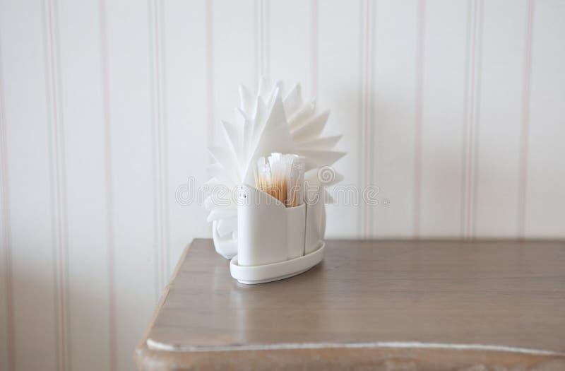 Tovaglioli bianchi in supporti sulla tavola di legno fotografia stock