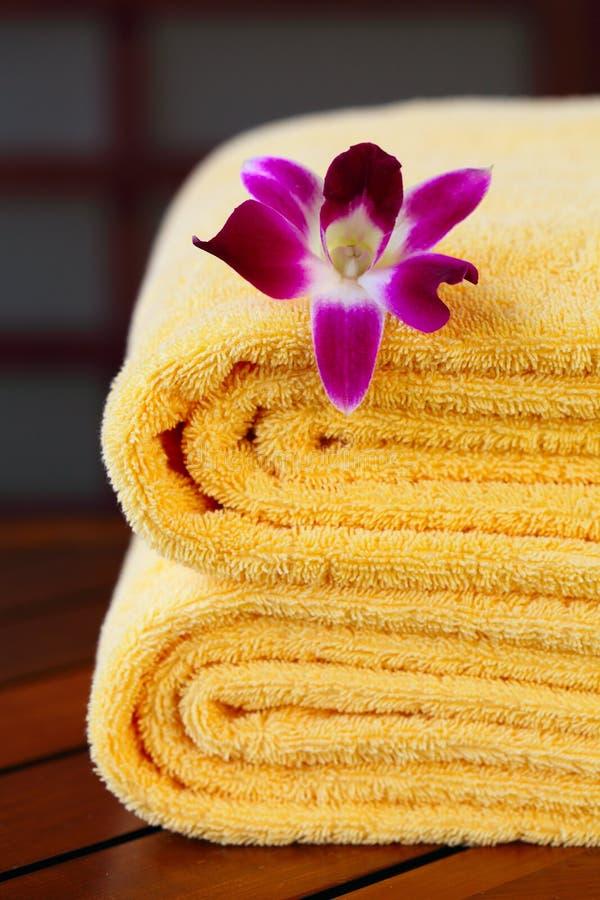Tovaglioli della stazione termale con l'orchidea fotografia stock
