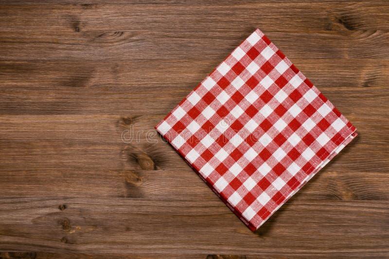 Tovagliolo bianco rosso piegato sulla tavola di legno immagini stock