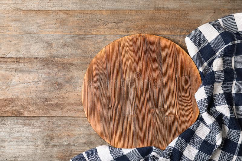 Tovagliolo del tessuto con il bordo del servizio e spazio per testo su fondo di legno immagini stock