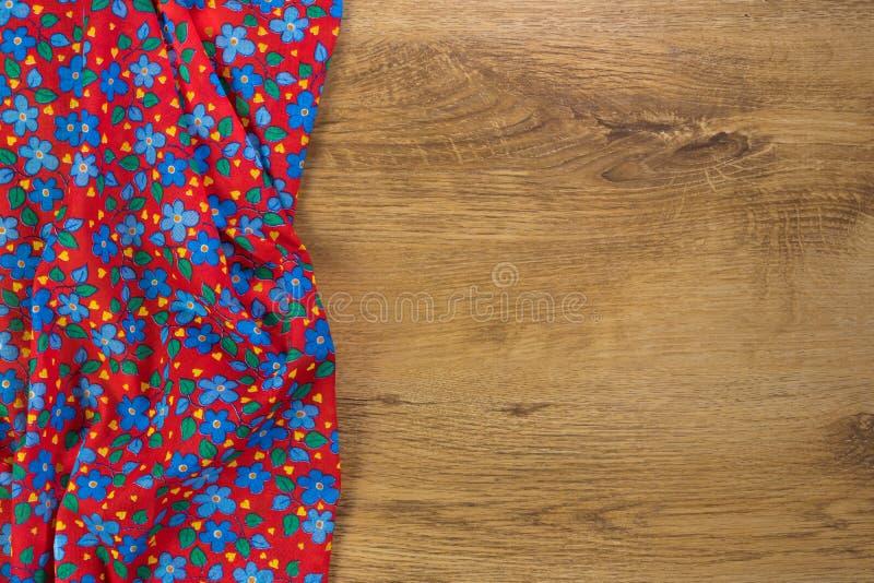 Tovagliolo floreale del panno del modello su fondo di legno vuoto fotografie stock libere da diritti