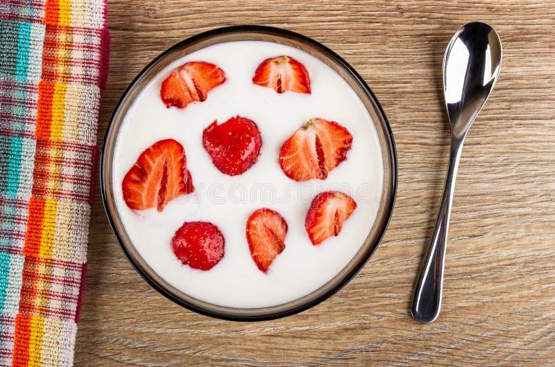 Tovagliolo, pezzi di fragole in ciotola marrone con yogurt, cucchiaio sulla tavola di legno Vista superiore immagini stock