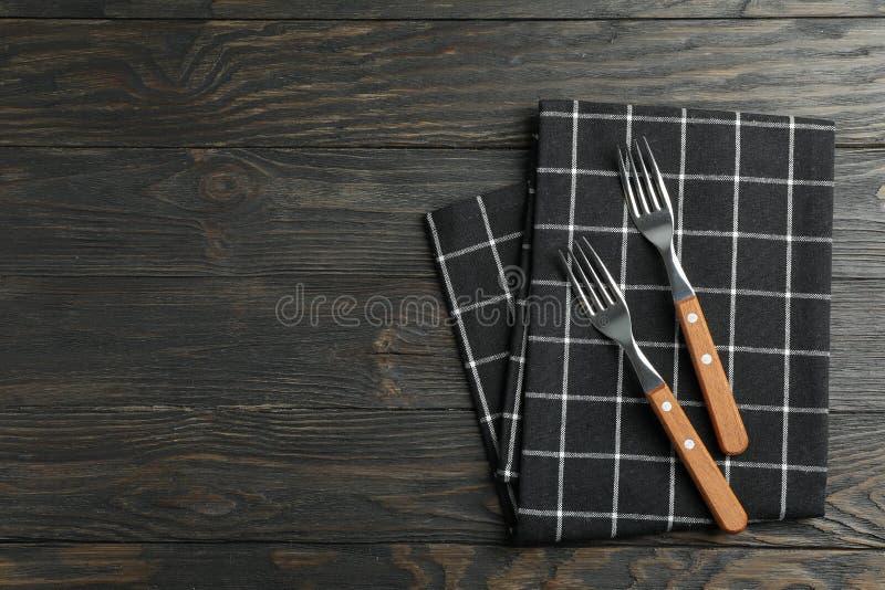 Tovagliolo piegato del tessuto con le forcelle su fondo di legno, vista superiore fotografia stock