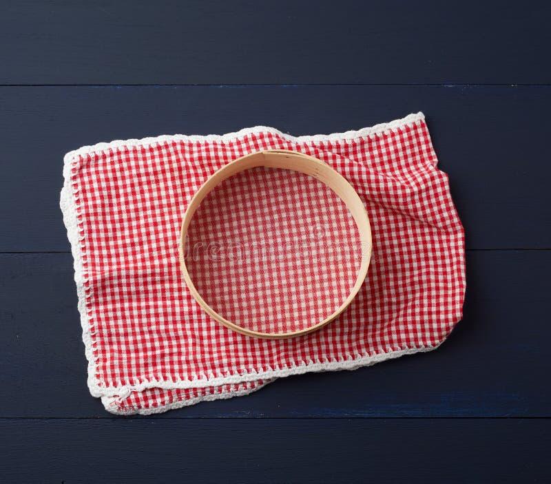 tovagliolo rosso tessile e setaccio rotondo per farina, sfondo di legno blu immagine stock
