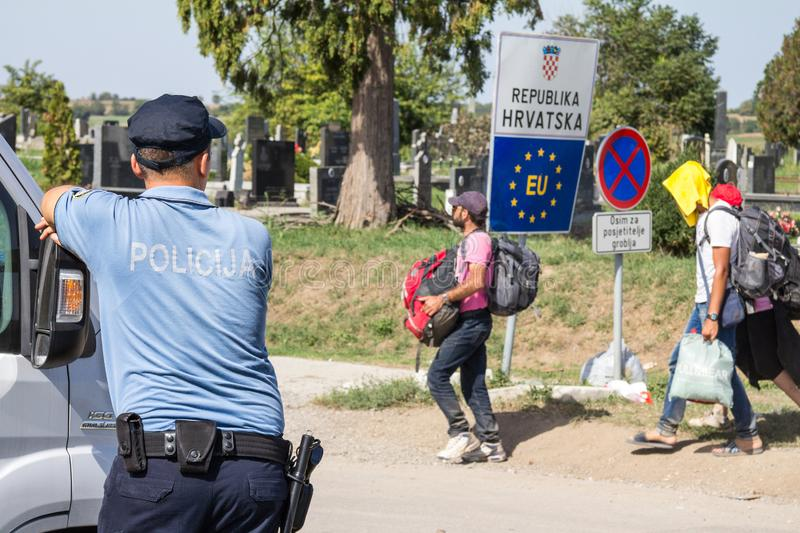 Croatian police officer looking at Refugees passing in front of the EU entrance sign on Serbia-Croatia border crossing of Tovarnik. TOVARNIK, CROATIA - SEPTEMBER stock photo