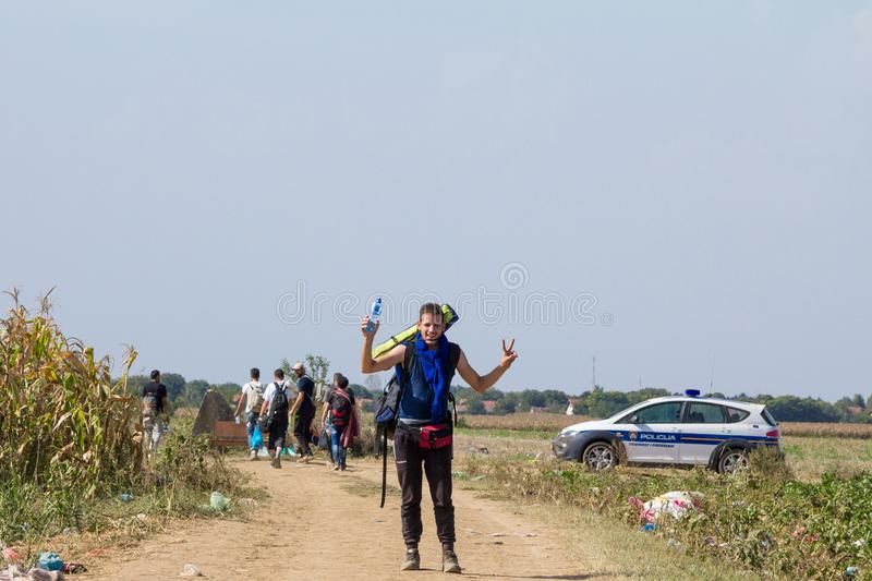Group of refugees, passing in front of a Croatian police car while crossing Serbia Croatia border in Tovarnik Sid. TOVARNIK, CROATIA - SEPTEMBER 19, 2015: Group royalty free stock images