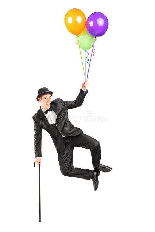 Tovenaar die omhoog in de lucht vliegt en ballons houdt stock foto's