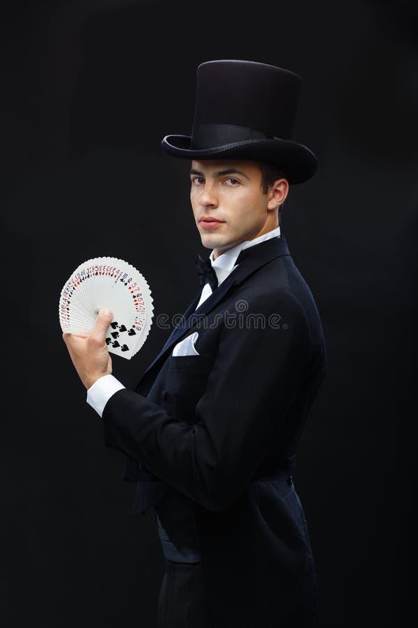 Tovenaar die truc met speelkaarten tonen royalty-vrije stock foto's