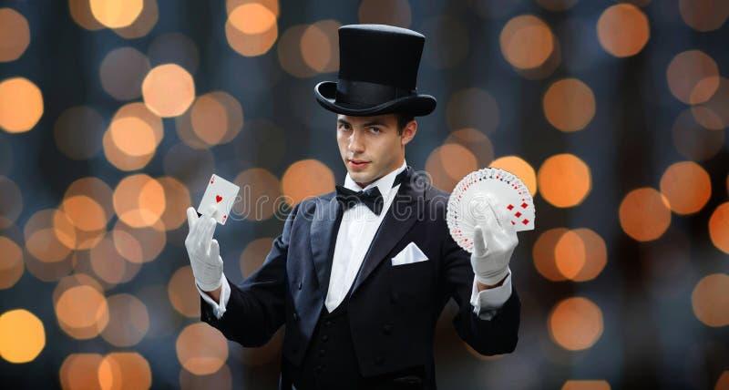 Tovenaar die truc met speelkaarten tonen stock afbeeldingen