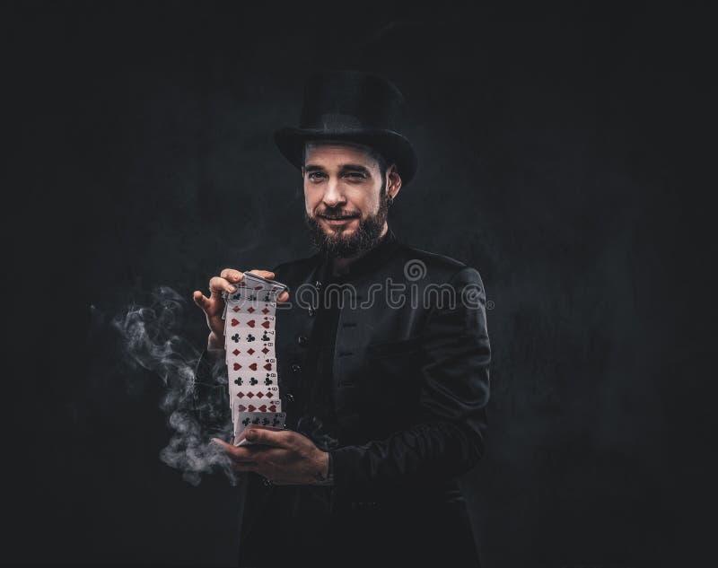 Tovenaar die truc met speelkaarten tonen stock foto's