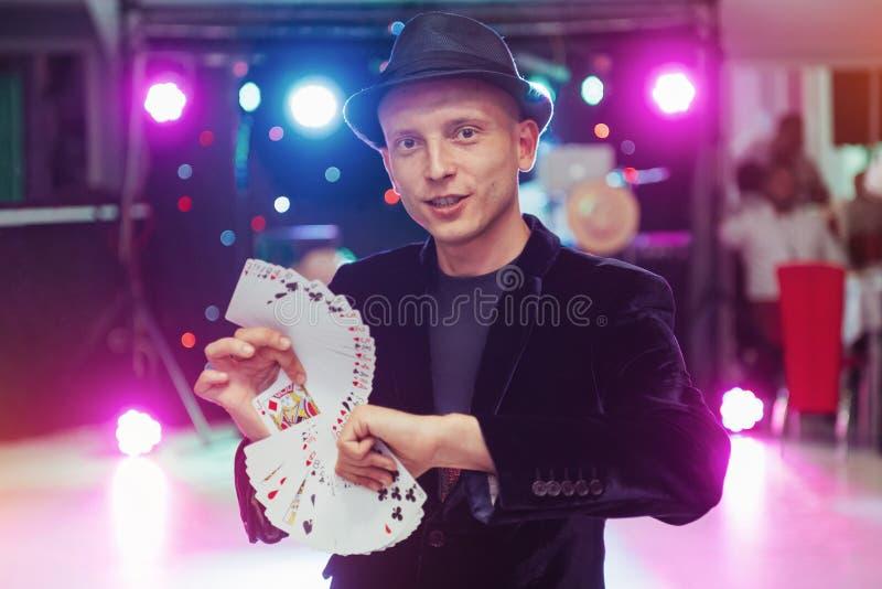 Tovenaar die truc met speelkaarten tonen Magisch, circus stock fotografie