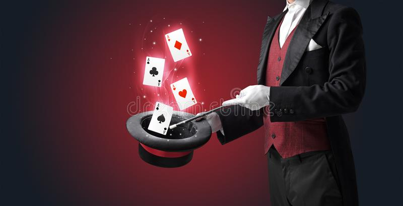 Tovenaar die truc met toverstokje en speelkaarten maken stock afbeeldingen
