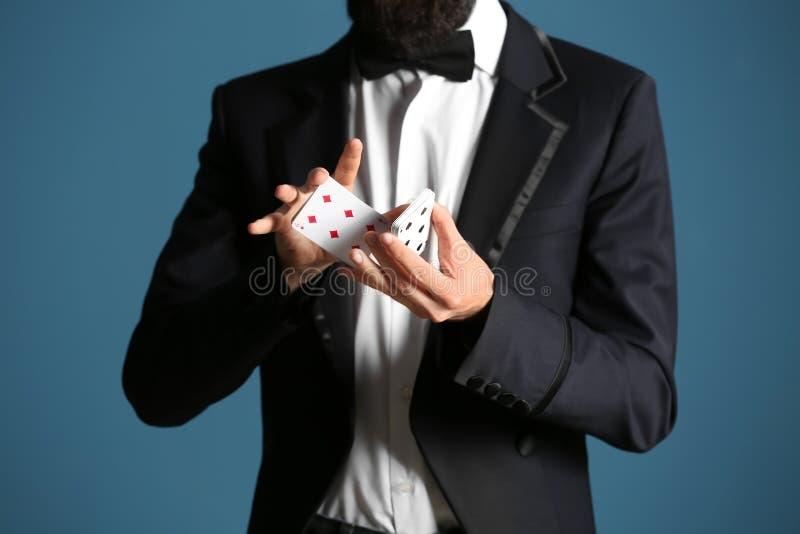 Tovenaar die trucs met kaarten op kleurenachtergrond tonen, close-up royalty-vrije stock afbeelding